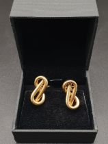 A PAIR OF 18K YELLOW GOLD EARRINGS IN A MODERNISTIC FIGURE 8 SHAPE. 7.91gms (small perforation to
