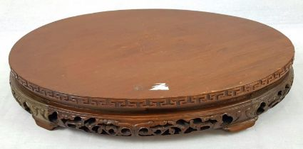 AN EARLY CHINESE OVAL SHAPED WOODEN STAND WITH TRADITIONAL DECORATION. 50 X 32cms 3.6kg