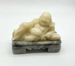 A VINTAGE WHITE JADE BUDDHIST FIGURE RECLINING ON MARBLE BASE. 1.83kgs 15 x 12cms