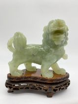 AN 19TH CENTURY JADE FOO DOG TEMPLE LION FIGURE ON WOODEN STAND. 496gms 12 x 10cms