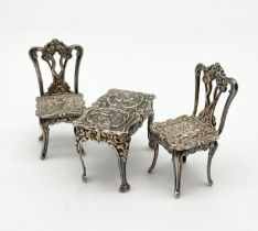 A HALL MARKED SILVER MINIATURE TABLE AND 2 CHAIR SET MADE BY A CHICK AND SONS. 34.3gms table