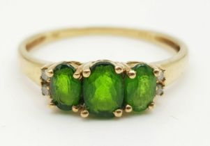 A 9K GOLD RING WITH GREEN TITANITE TRILOGY FLANKED BY 2 SMALL DIAMONDS ON EACH SIDE. 1.45gms size P