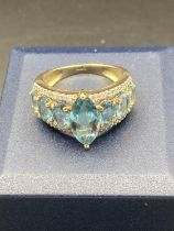 9 carat Gold Ring having Blue Aqua stones set in baguette and oval form to top. 3.9 grams. Size M1/2