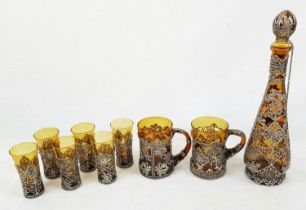 A VINTAGE RUSSIAN AMBER GLASS DRINKING SET DECORATED WITH WHITE METAL. TO INCLUDE A TALL