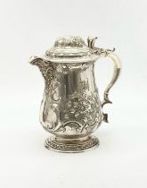 A MAGNIFICENT HAND CHASED SILVER PLATE LIDDED JUG. 745gms 22cms