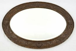 A VINTAGE WOODEN FRAMED OVAL MIRROR. 93 X 69cms