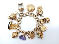 A Vintage 9K Yellow Gold Charm Bracelet with Eleven Eclectic 9K Yellow Gold Charms - Some with