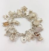STERLING SILVER CHARM BRACELET WITH 20 CHARMS. 84.2G