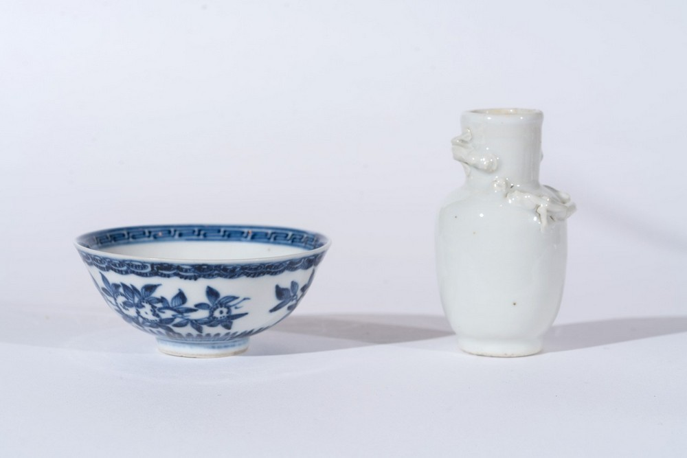 Arte Cinese A small white porcelain vase decorated with moulded chilong and small blue and white po