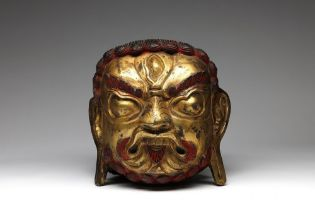Arte Himalayana  A large gilded copper embossed head of Mahakala Tibet, 19th century .