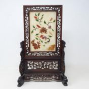 A Chinese table screen, with a pierced hardwood frame, the screen inset with hard stones in floral