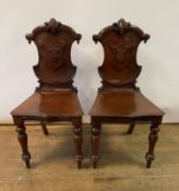 A pair of Victorian mahogany hall chairs, with cartouche shaped backs and turned front legs (2)