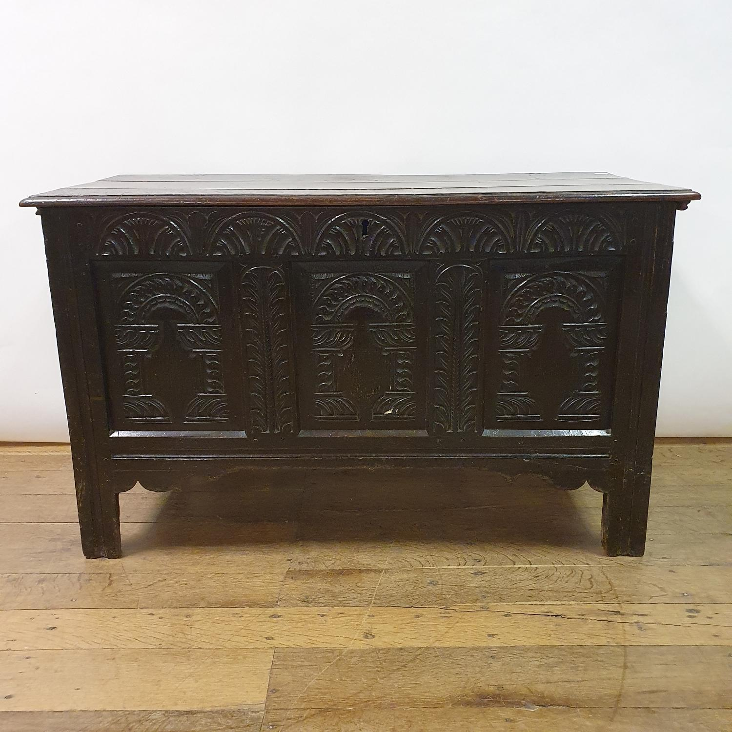 An 18th century oak coffer, with later carved decoration, 123 cm wide