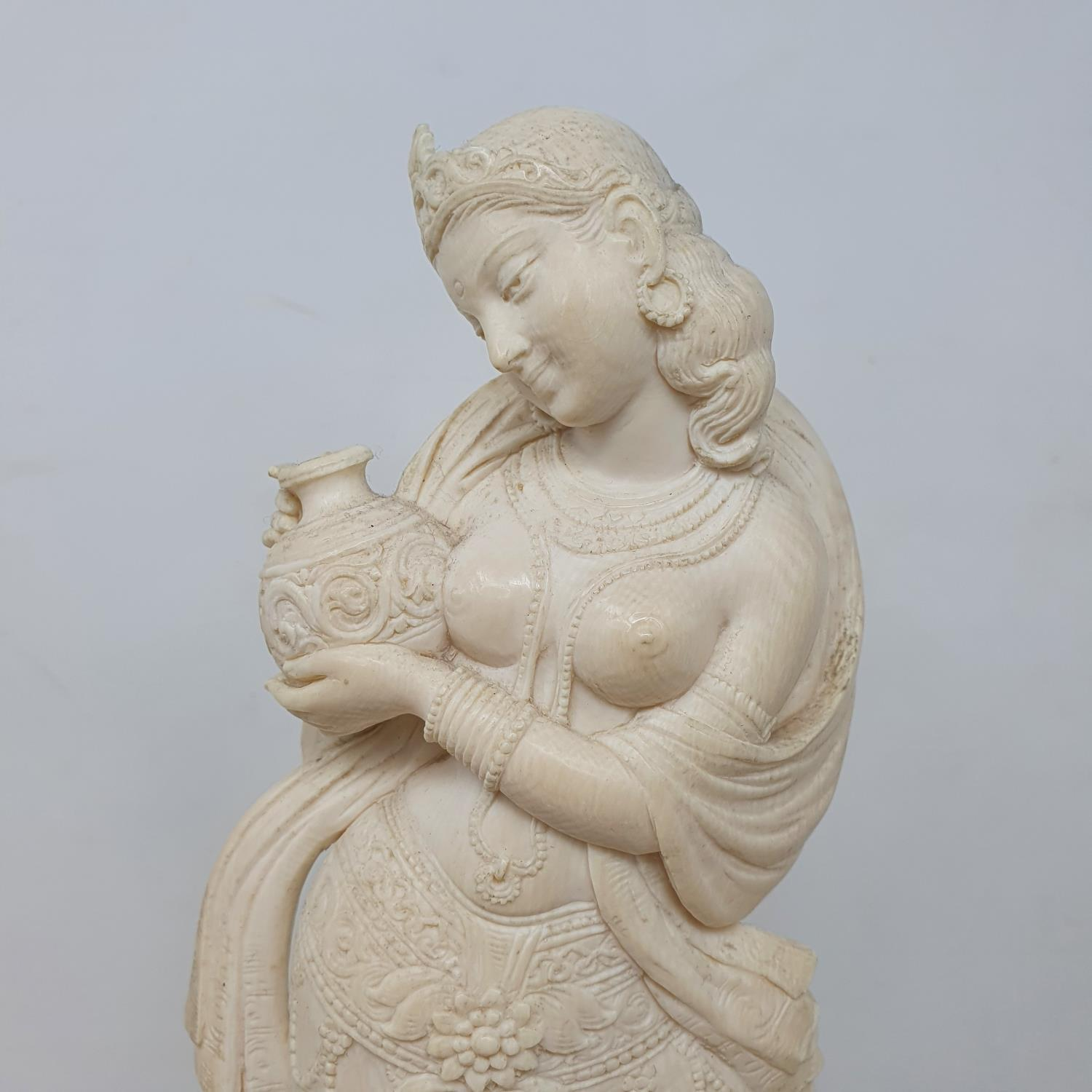 An early 20th century Indian carved ivory figure, of a woman holding a vase, on a wooden base, 28 cm - Image 4 of 4