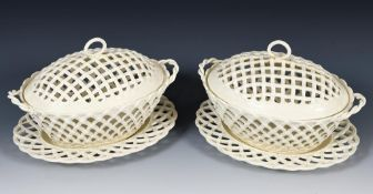 A pair of late 18th/early 19th century Leeds creamware basket and covers, on stands, 31 cm wide