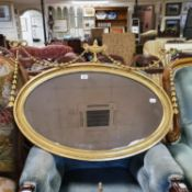 An oval gilt wall mirror, with a vase finial, 90 cm wide, and another mirror (2)
