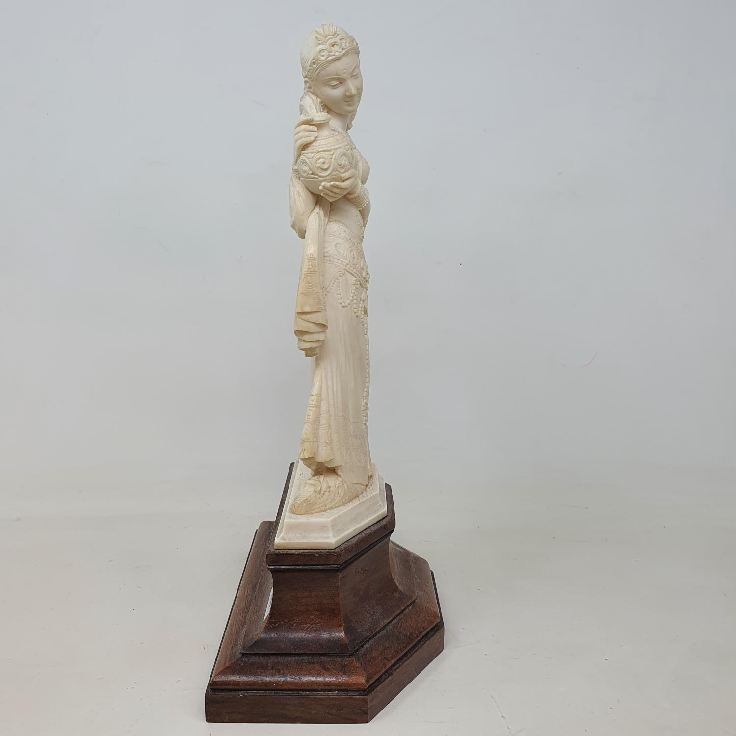An early 20th century Indian carved ivory figure, of a woman holding a vase, on a wooden base, 28 cm - Image 2 of 4