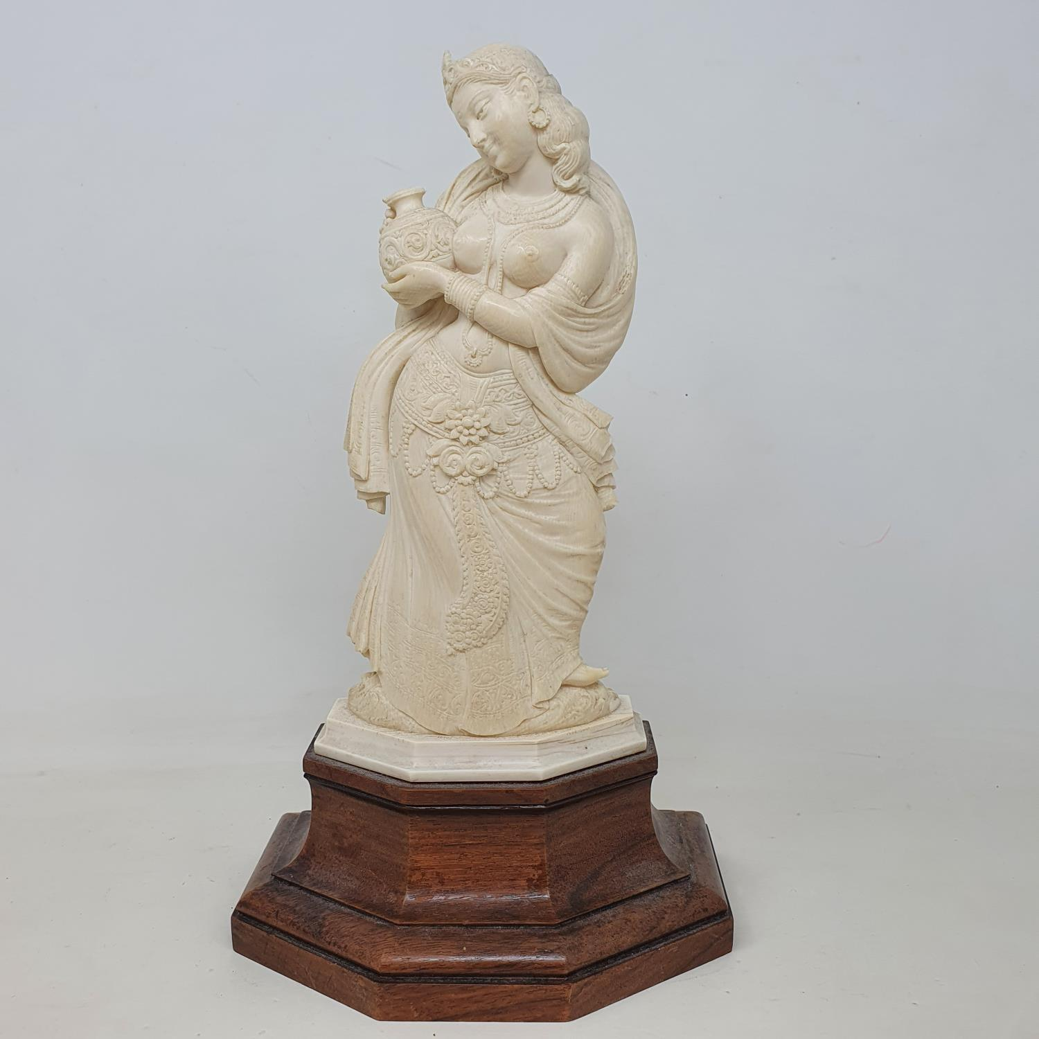 An early 20th century Indian carved ivory figure, of a woman holding a vase, on a wooden base, 28 cm