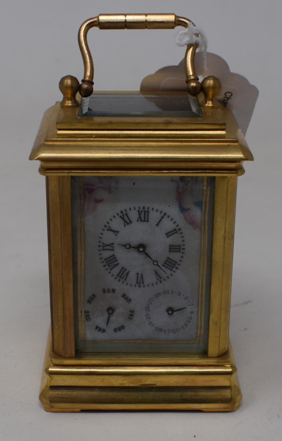 A modern brass carriage clock, inset with painted porcelain panels, 10 cm high
