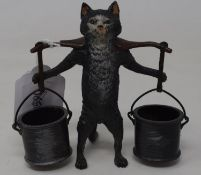 A modern novelty match strike in the form of a cat carrying two buckets, 10 cm high