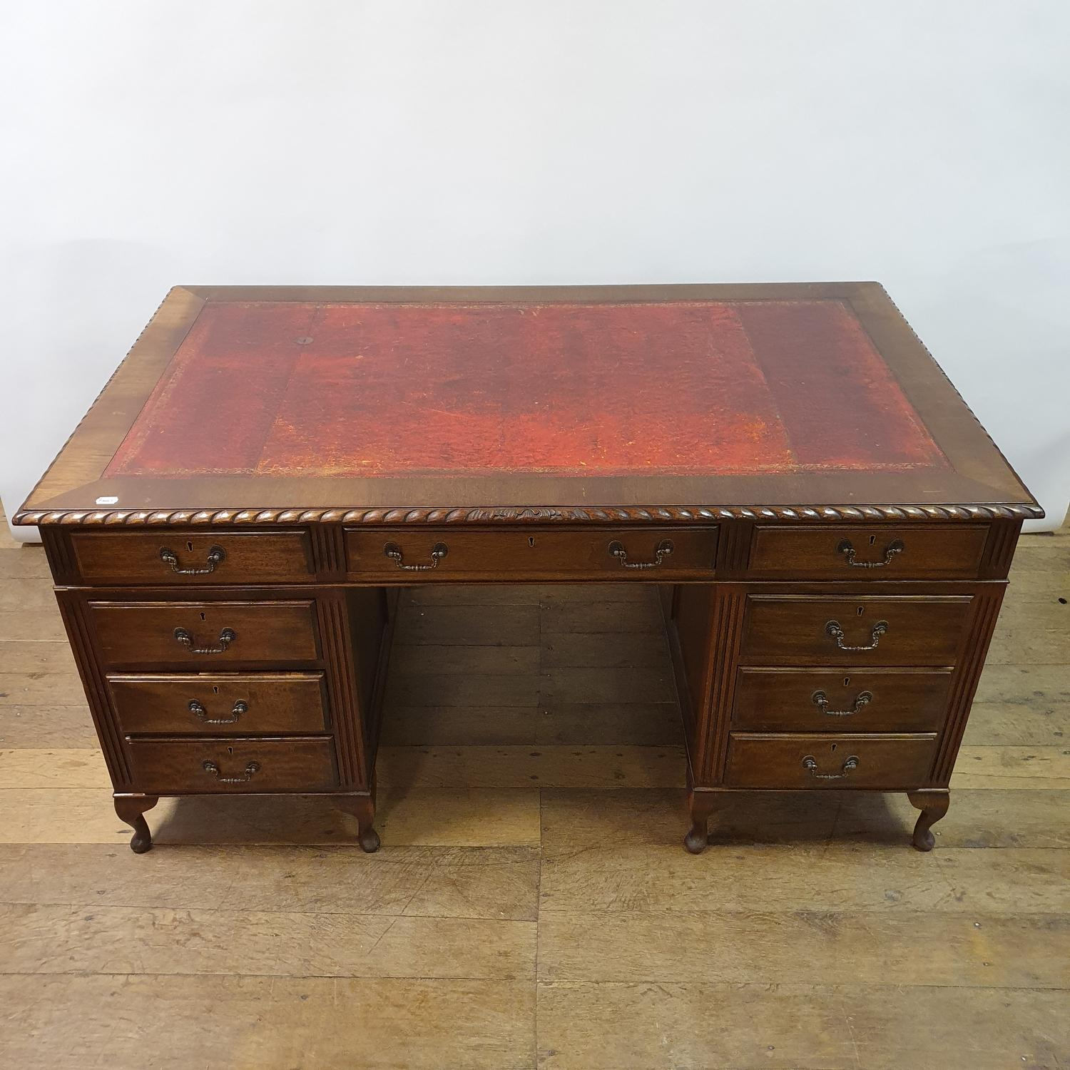 A mahogany pedestal desk, the leather inset top above an arrangement of nine drawers, on dwarf