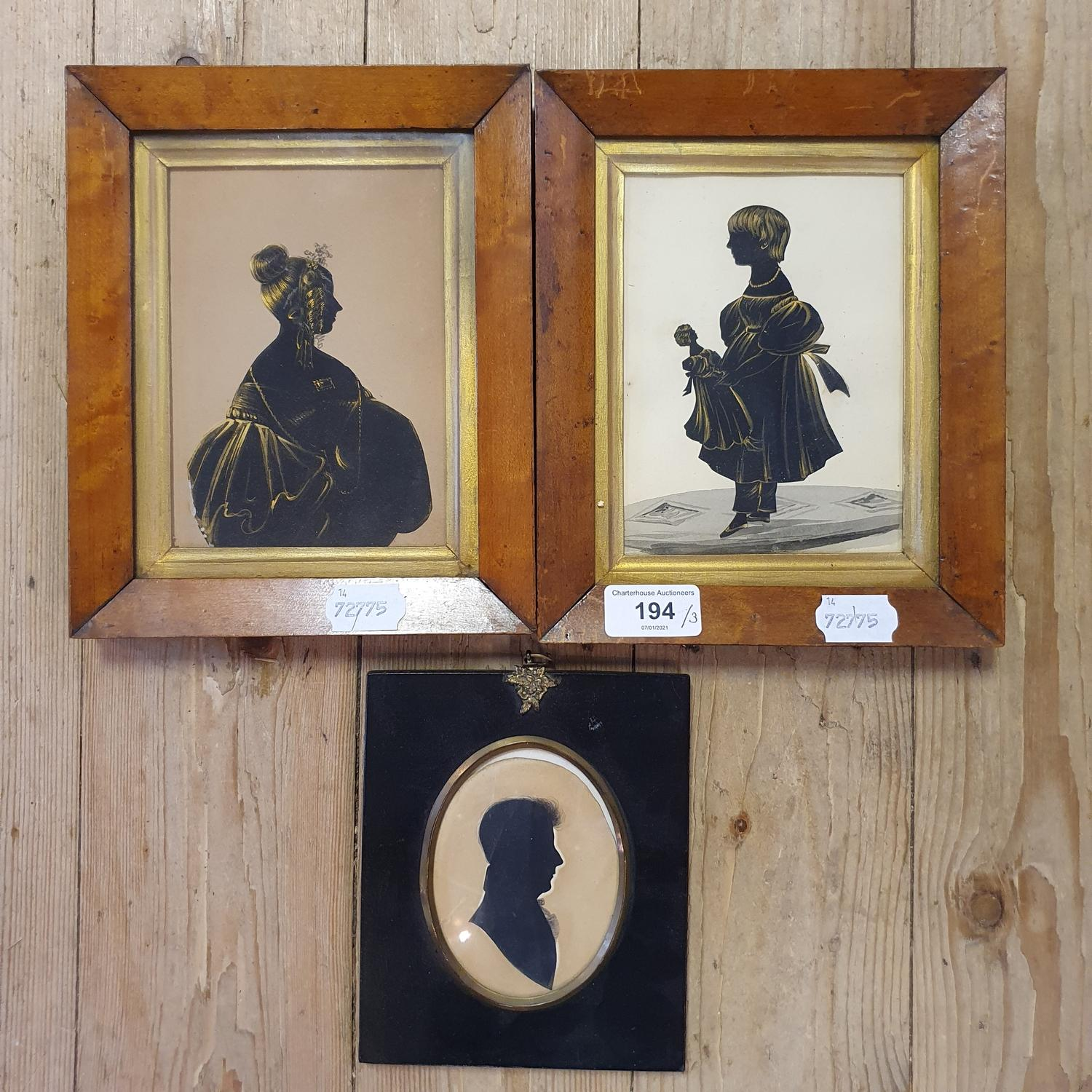 A Victorian bronze tinted silhouette of a girl holding a doll, 15 x 11 cm, her pair, possibly her