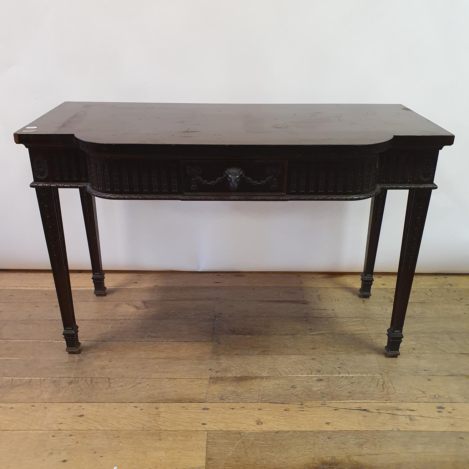 An early 20th century Adams revival mahogany side table, having a frieze drawer with carved rams