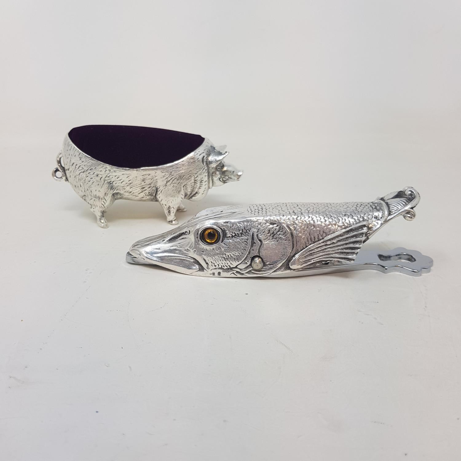 A modern silver plated paperclip in the form of a pike, and a modern pincushion in the form of a pig