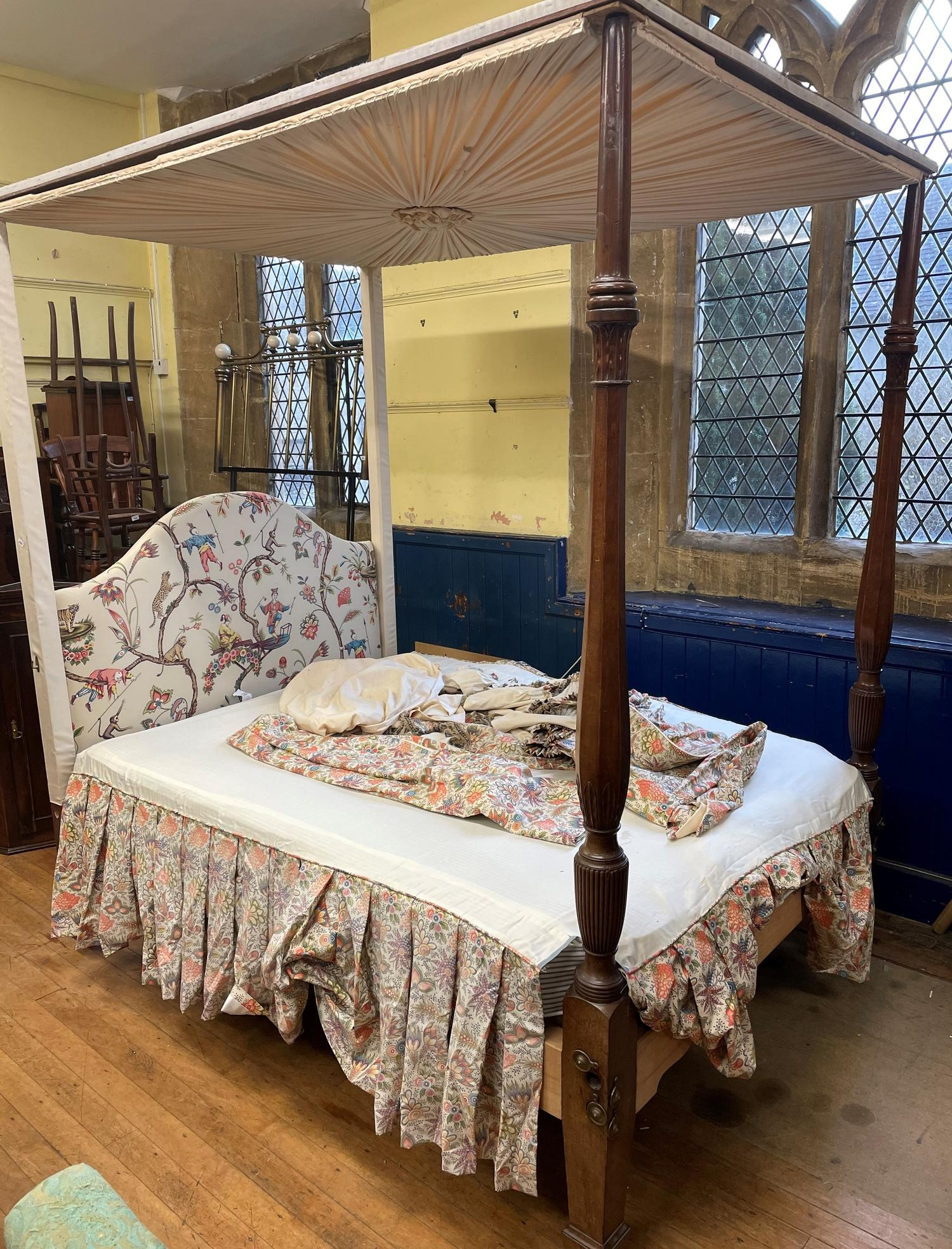 A George III style mahogany four poster bed, on octagonal baluster ends with leaf carved and