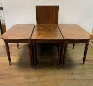 An early 19th century mahogany extending dining table, with a central drop leaf section and an extra