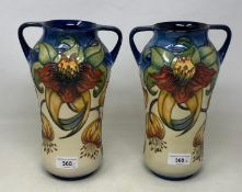 A pair of Moorcroft pottery vases, decorated flowers, with two handles and of waisted form, 25.5