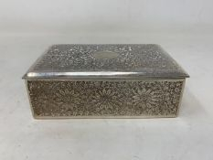 A Persian silver coloured metal table cigarette box, decorated flowers and foliage, 13.5 cm wide