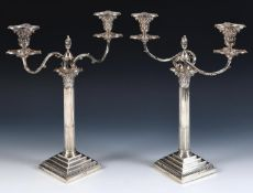 A pair of late Victorian silver Corinthian column table candelabra, with stepped square bases and