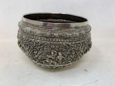 A Burmese style silver coloured metal bowl, embossed figures and foliage, dented and holed, 13 cm