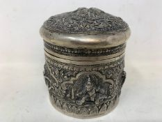 A Burmese silver coloured metal cylindrical box and cover, embossed figures, the base engraved a
