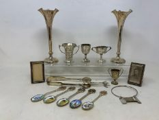 A pair of silver spill vases, Birmingham 1902, loaded, 17 cm high, four small silver trophy cups,
