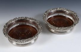 A pair of early 19th century Scottish silver wine coasters, with rococo style edges, a reeded