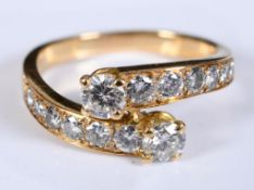 A yellow coloured metal crossover ring, set two rows of seven graduated diamonds, approx. ring