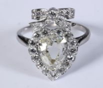 A white coloured metal ring, in the form of a bow above a heart, the heart with a central pear cut