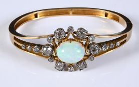 A late Victorian/Edwardian yellow coloured metal bangle, set an opal within a surround of