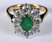 An 18ct white and yellow gold, oval emerald and diamond cluster ring, the central emerald approx.
