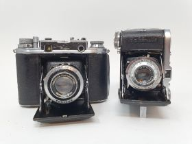 An Ensign Commando folding camera, and a Balda folding camera, with a leather outer case (2)