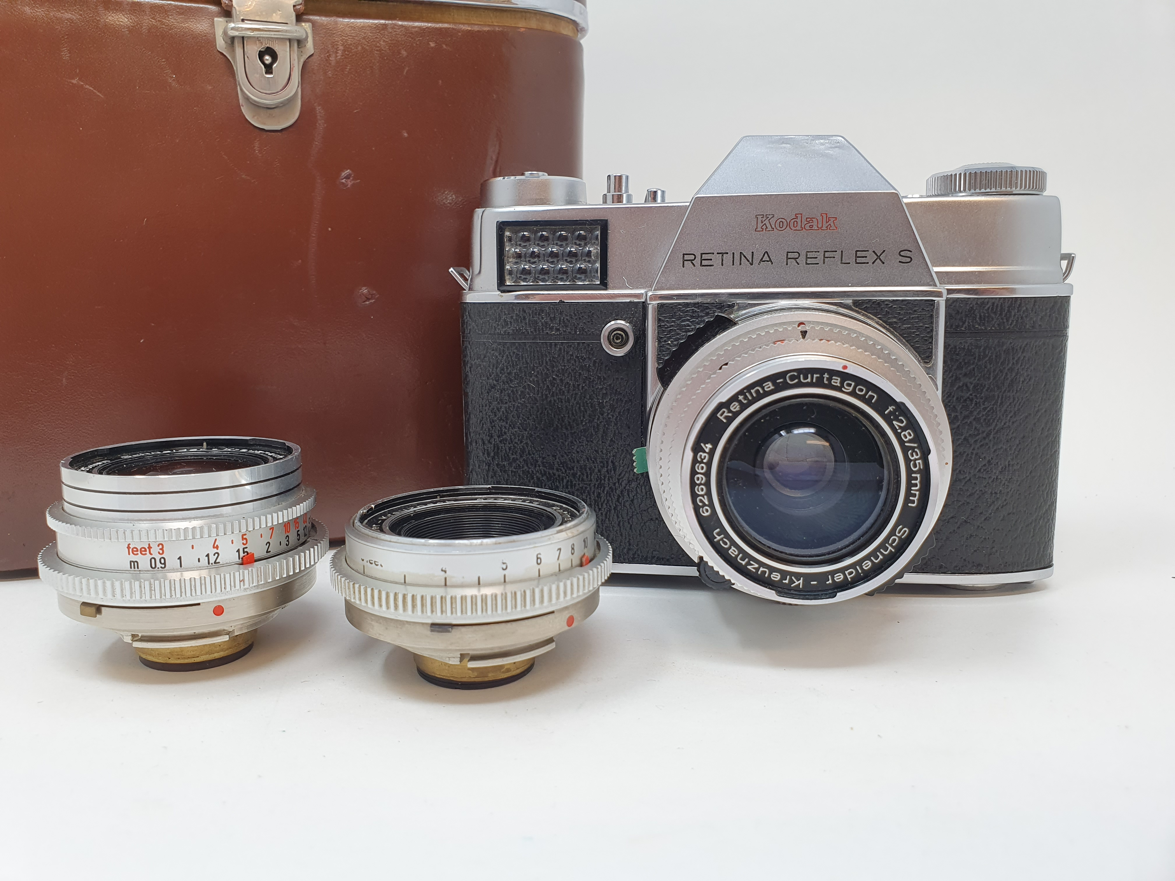 A Kodak Retina Reflex S, serial number 80495, with two extra lenses, in leather carrying case