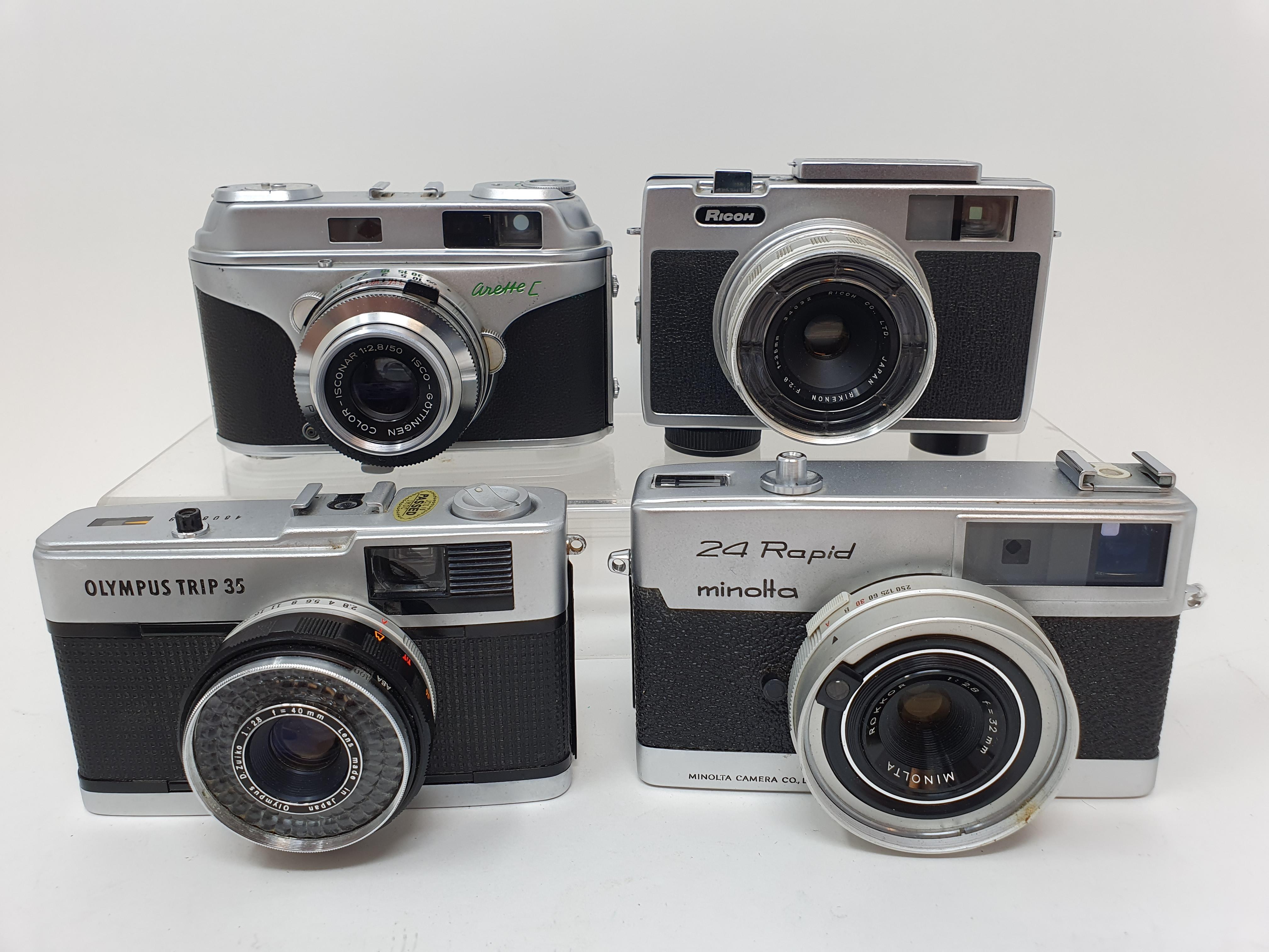 A Minolta 24 Rapid camera, an Arette C camera, a Ricoh Auto 126 camera, and an Olympus Trip 35