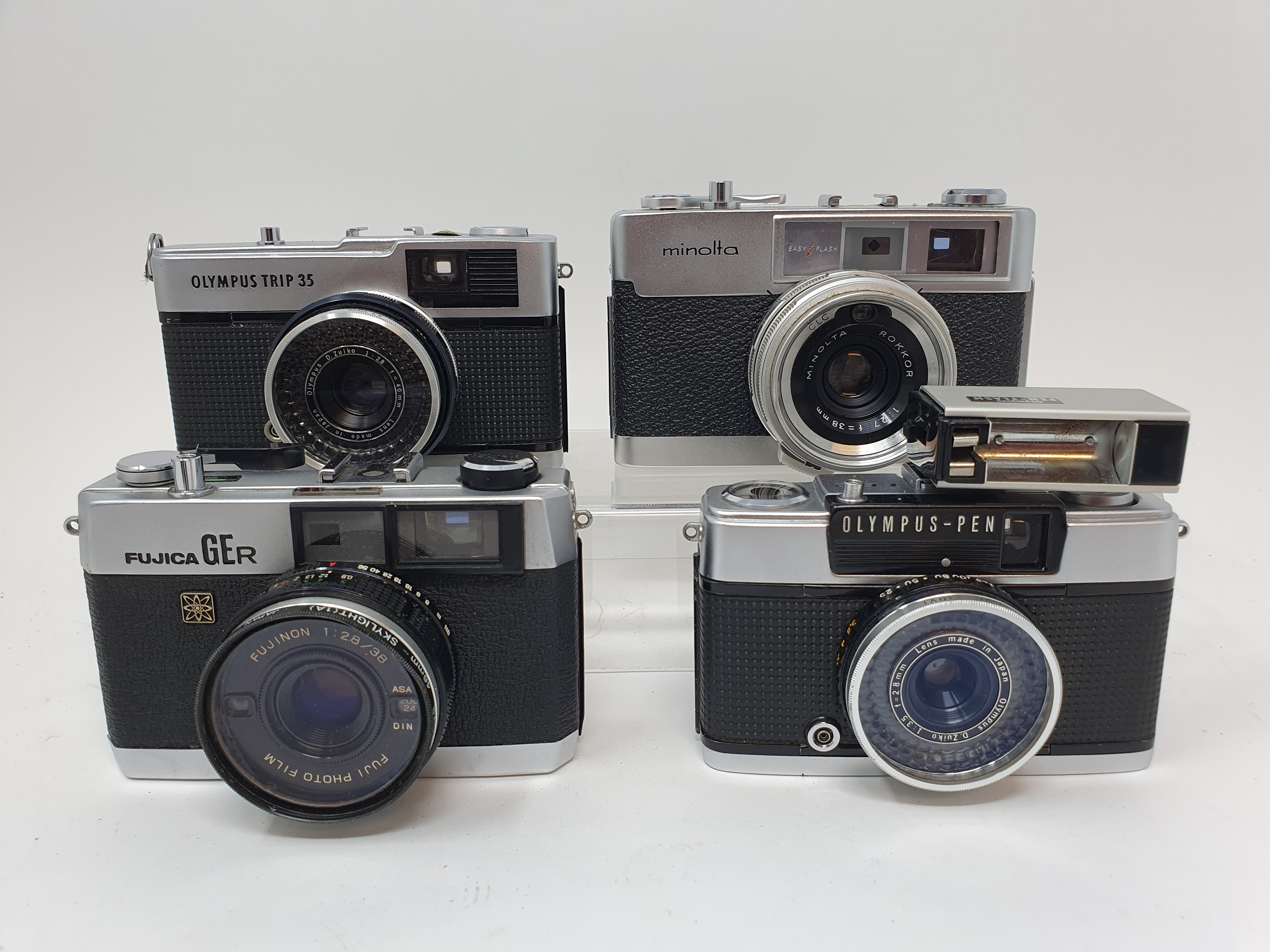 An Olympus Trip 35 camera, an Olympus - PEN camera a Fujica GER camera and a Minolta AL - F