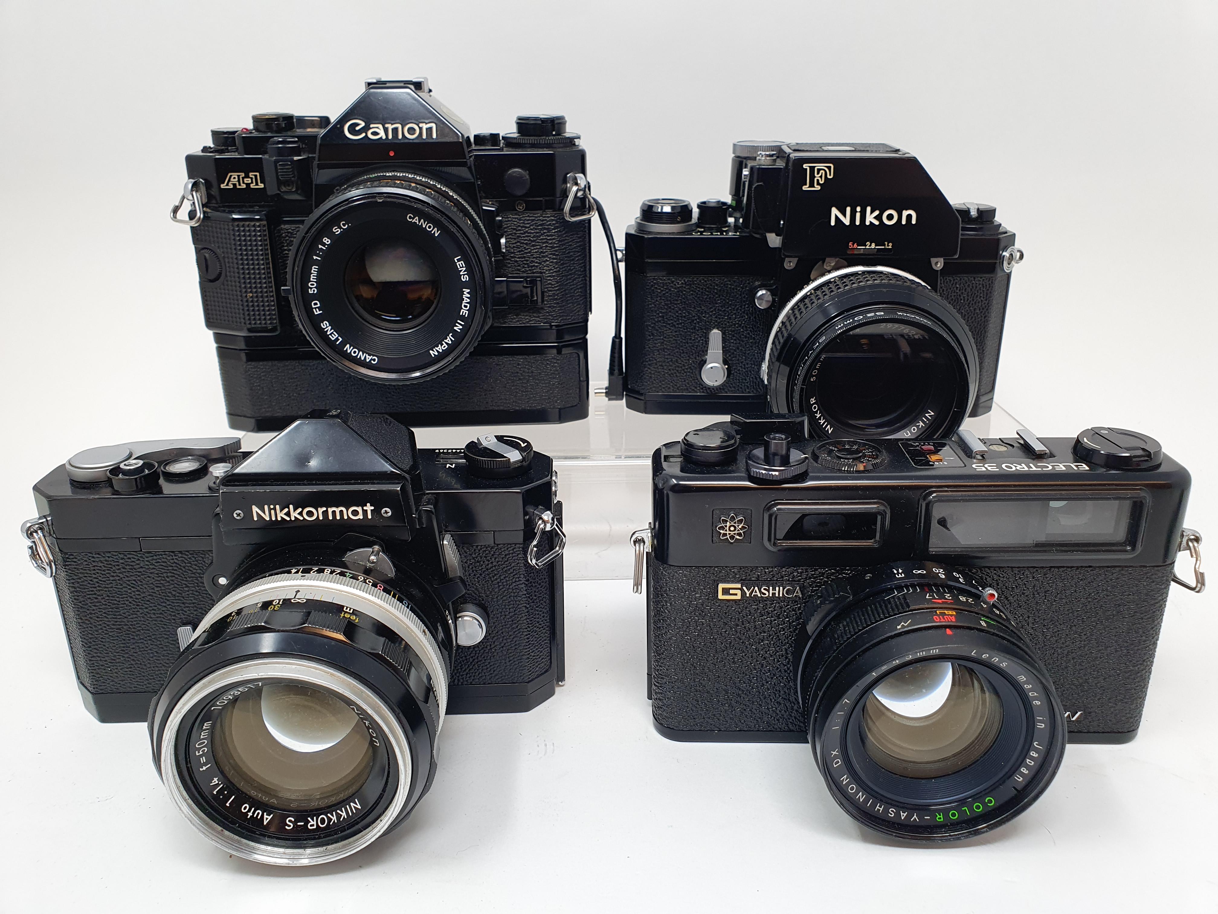 A Nikon F camera, with outer case, a Yashica GTN camera, a Canon A-1 camera, and a Nikkormat Nikon