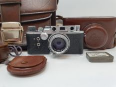 A Reid & Sigrist ltd camera, serial number P2750, with leather outer case, lens, and accessories