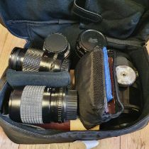 A Pentacon camera les and six other camera lenses and a camera bag Provenance: Part of a vast single