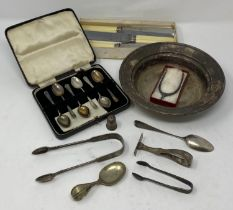 A pair of silver sugar tongs in the form of a wishing bone, assorted silver spoons, and silver plate