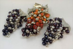 A silver coloured metal and painted grape and vine table ornament, 31 cm wide and two others similar
